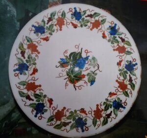 multi coloured stones inlay work on white marble tabletop