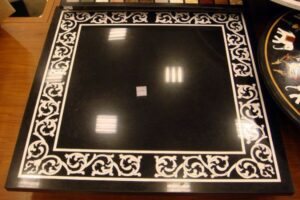 white stones inlay work on black marble tabletop